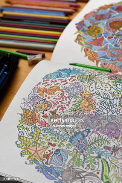 Adult coloring book on table with color pencils