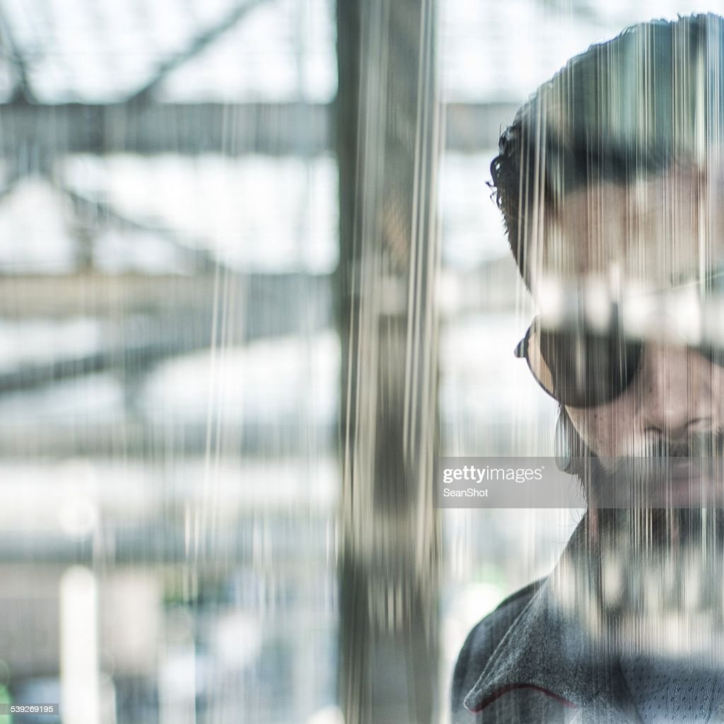 Adult Cool Hipster Looking Through Filtered Glass Door Stock Photo