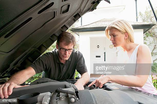 Adult couple checking under car hood