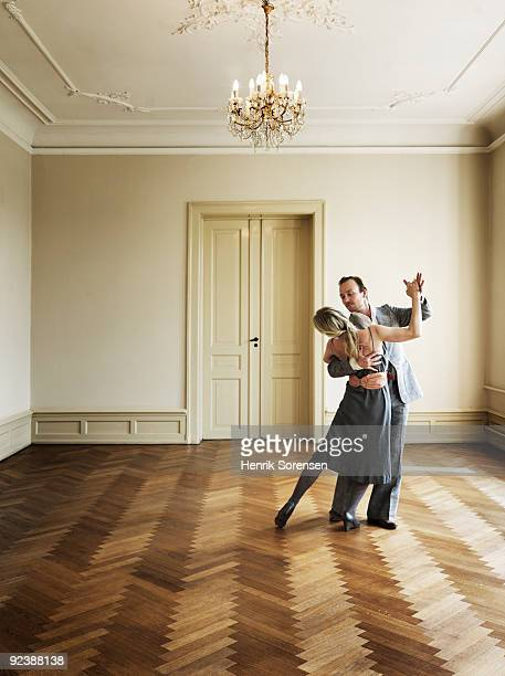 Adult couple dancing in empty interior