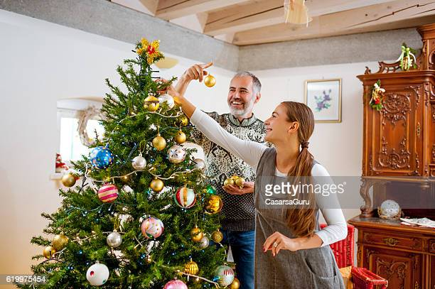 Adult Couple Decorating the Christmas Tree