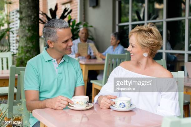 Adult couple enjoying a cup of coffee at a cafeteria smiling
