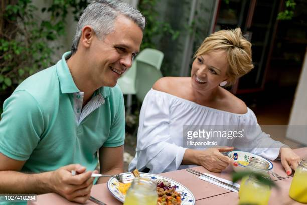 adult couple enjoying a lunch outside looking very happy - hispanolistic stock photos and pictures