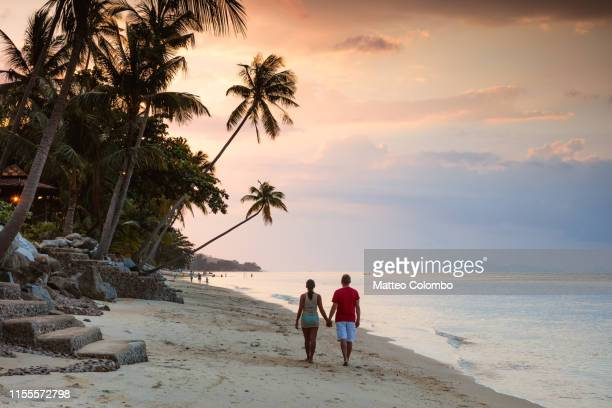 adult couple hand in hand on beach at sunset, thailand - thailand stock pictures, royalty-free photos & images