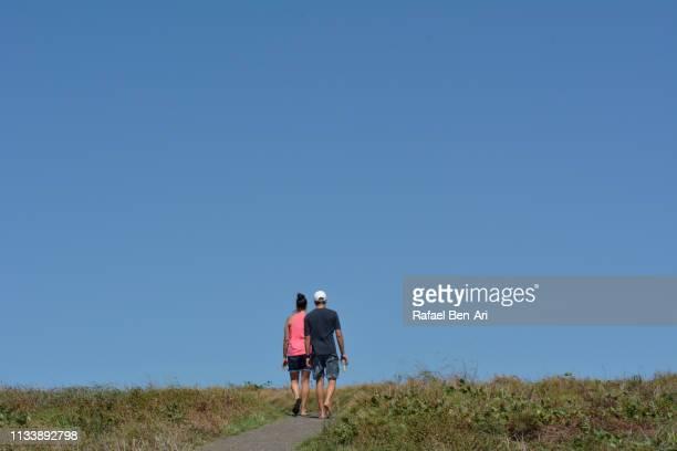 adult couple hiking outdoors - rafael ben ari stock-fotos und bilder