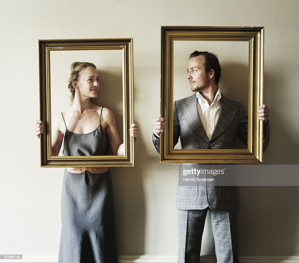 Adult Couple Holding Up Frames Stock Photo | Getty Images