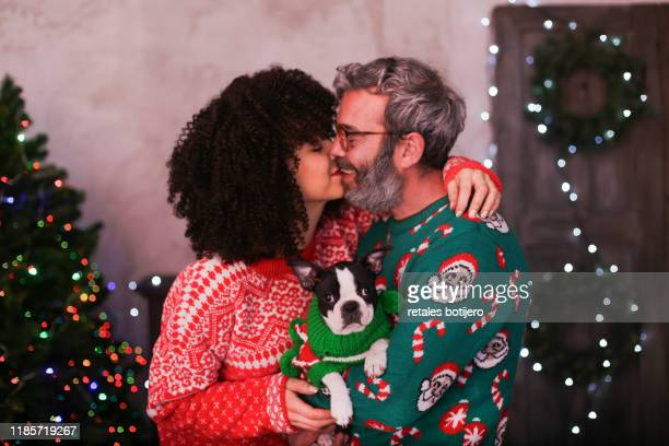 adult couple kissing at christmas time - tradition stock pictures, royalty-free photos & images
