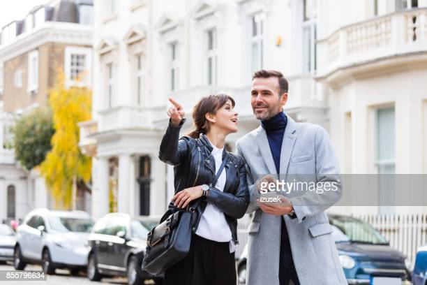 adult couple looking aroung in the city street - time of day stock pictures, royalty-free photos & images