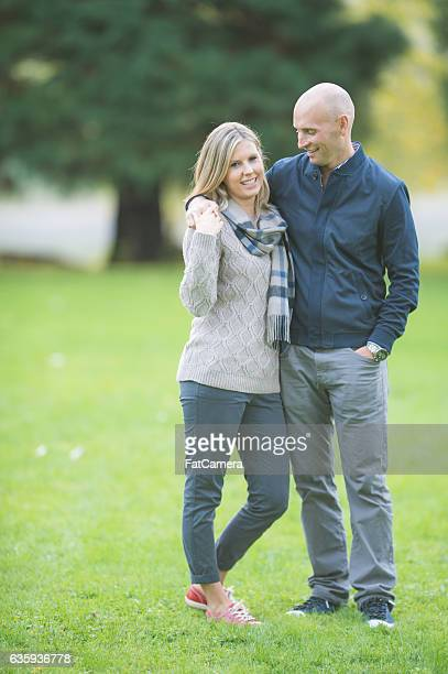 adult couple posing together in a park on a sunny - 30 39 years stock pictures, royalty-free photos & images