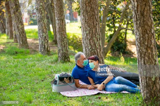 adult couple relaxing in public park with pets during coronavirus pandemic - stock photo - picnic stock pictures, royalty-free photos & images