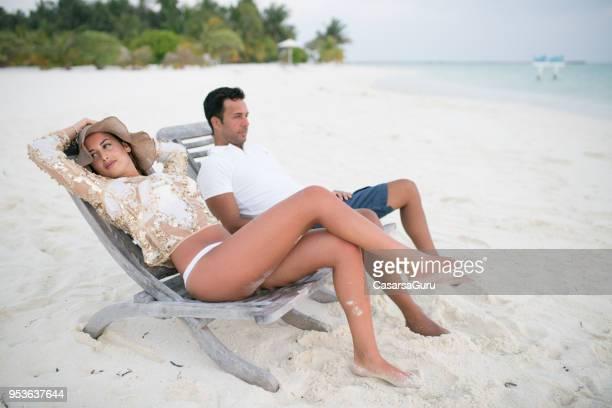 Adultos pareja relajarse en tumbonas en la playa de arena