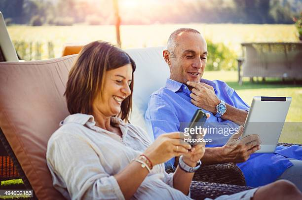 Adult couple relaxing with digital tablet at resort