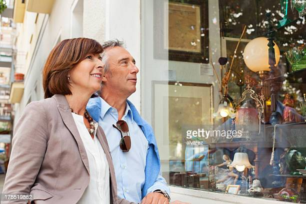 adult couple shopping in an antique shop - mid volwassen koppel stockfoto's en -beelden