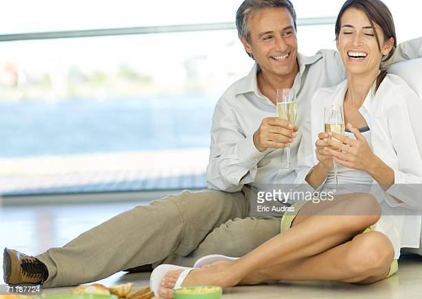 Adult couple sitting on floor, holding champagne flutes