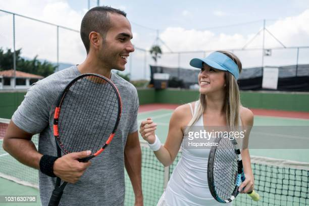 adult couple tennis players talking after ending the game looking very happy - tennis player stock pictures, royalty-free photos & images