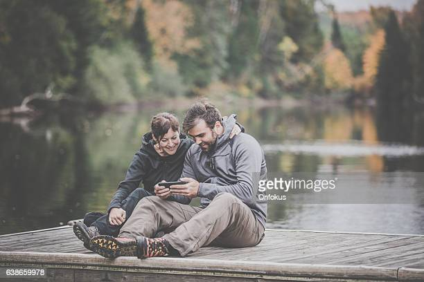 Adult Couple Using Smart Phone in Nature