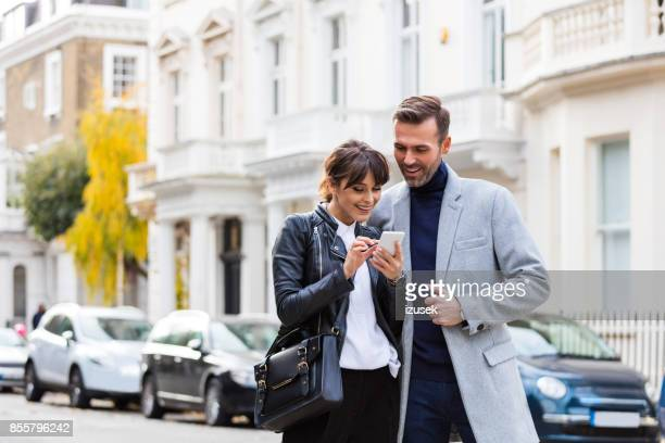 adult couple using smart phone together in the city street - searching stock pictures, royalty-free photos & images