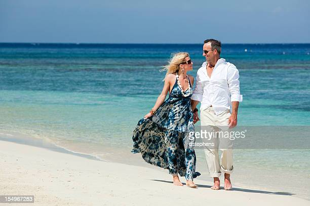 Adult Couple Walking Along Tropical Beach