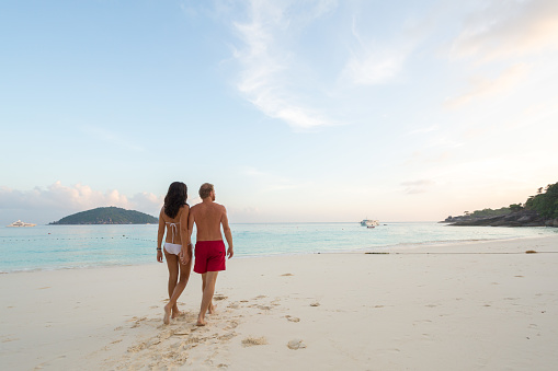 Adult couple walking hand in hand on a beach - gettyimageskorea