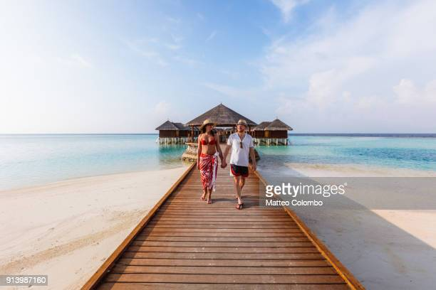 adult couple walking on jetty, maldives - tourist resort stock pictures, royalty-free photos & images