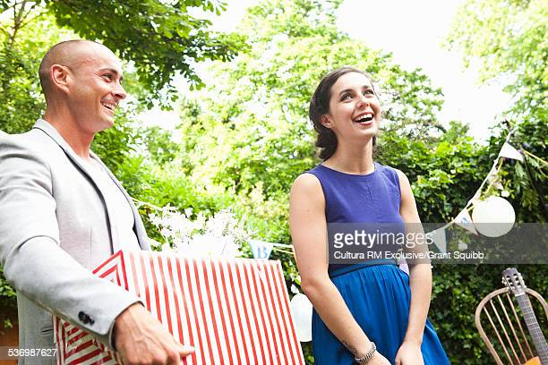 Adult couple with birthday gift at garden party