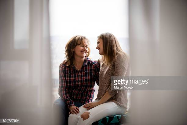 adult daughter and mother conversing at window - mother daughter stock photos and pictures
