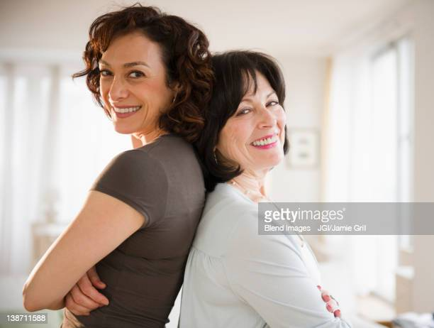 Adult daughter and mother standing back to back