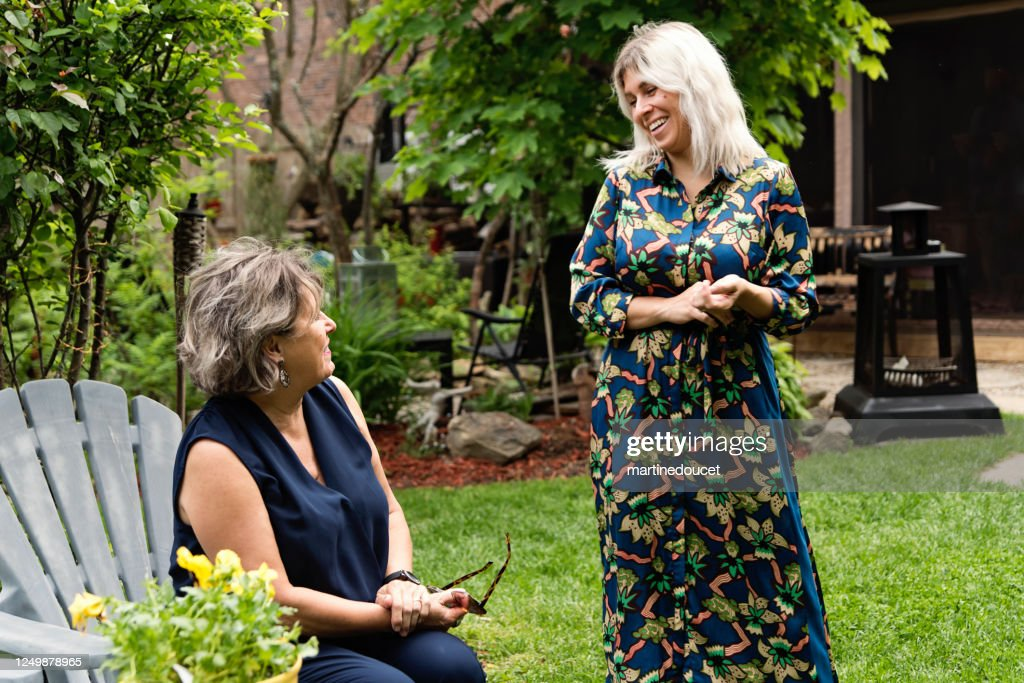 Adult daughter and senior mother chatting backyard. : Stock Photo