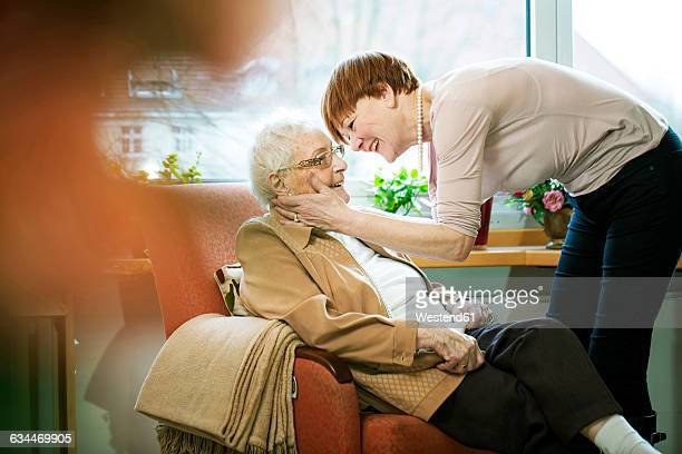 adult daughter greeting her mother with alzheimer's disease in her room at retirement home - older woman bending over stock pictures, royalty-free photos & images