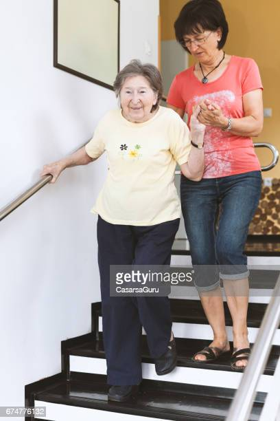 adult daughter helping senior mother walking on stairs - residential care stock photos and pictures