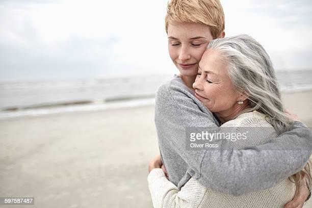 adult daughter hugging senior mother on the beach - umarmen stock-fotos und bilder