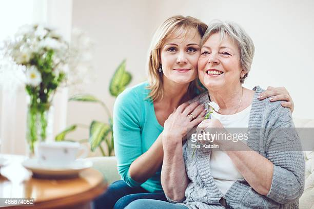 Adult daughter is hugging her mother