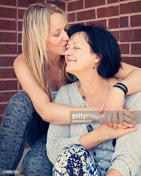 Adult daughter kissing mature mother forehead outdoors.