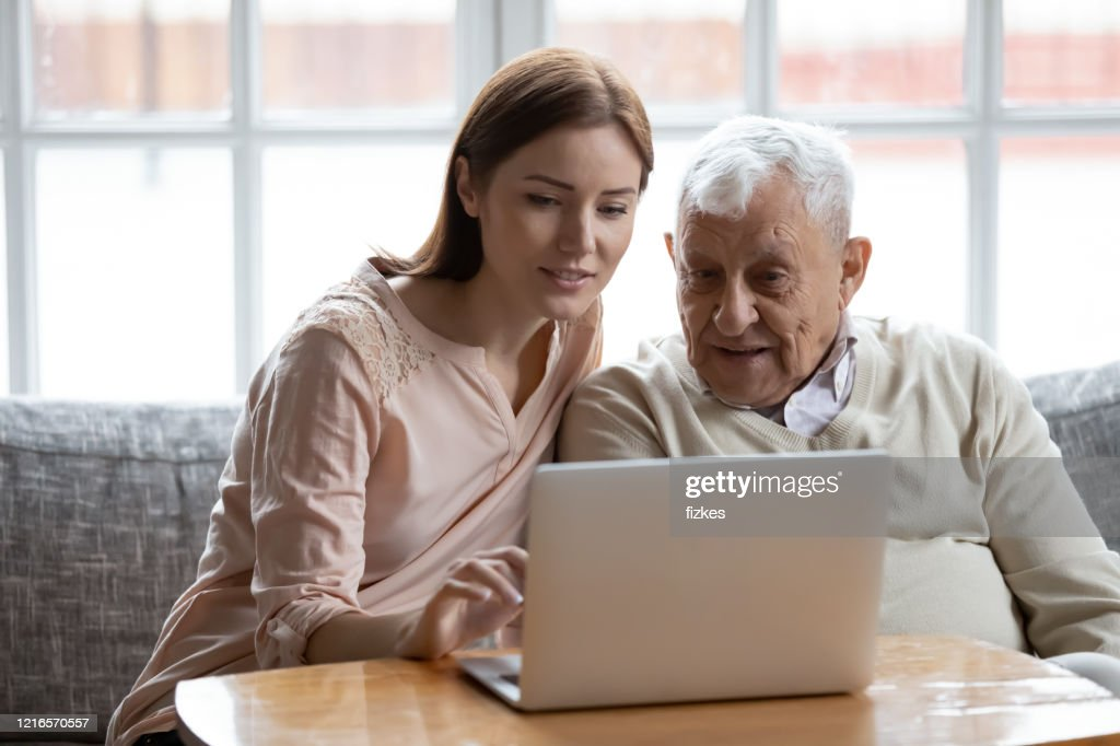 Adult daughter old father choose services via internet using computer : Stock Photo