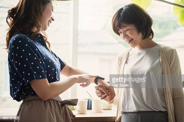 Adult daughter showing a smart watch to mother