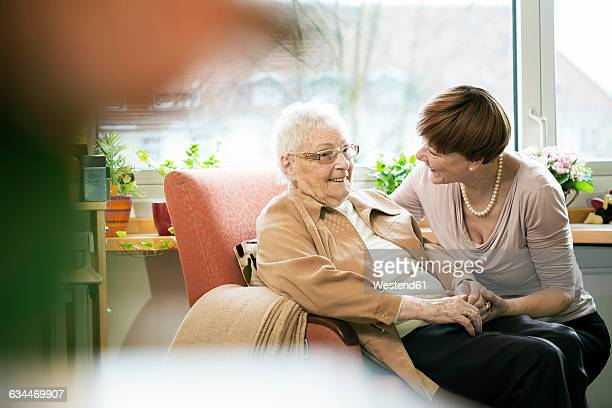Adult daughter talking to her mother with Alzheimers disease in her room at retirement home