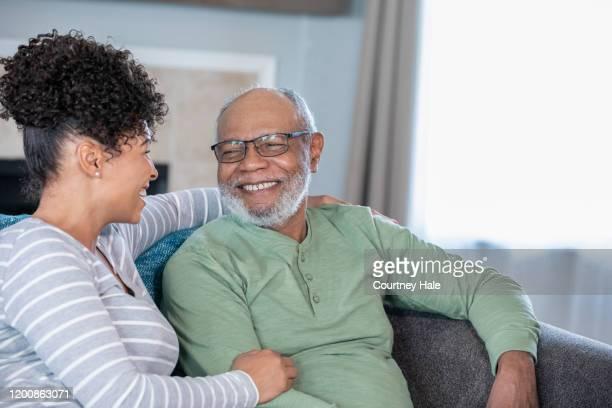 volwassen dochter bezoekt senior vader in begeleid wonen thuis - gezondheidszorg beroep stockfoto's en -beelden