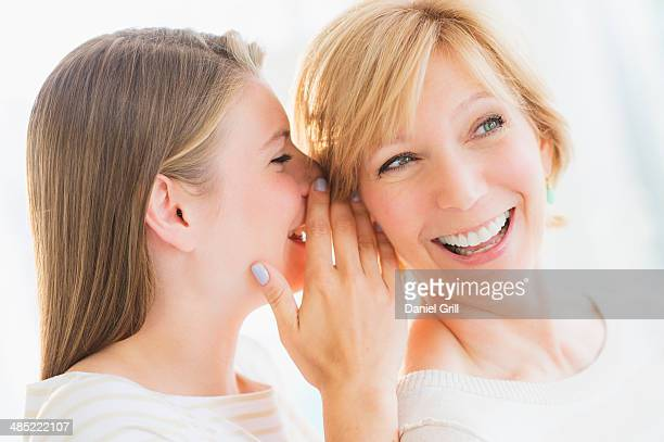 Adult daughter whispering into mother's ear