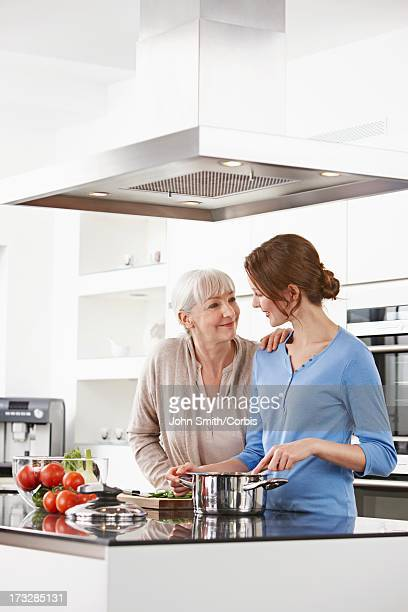Adult daughter with mother in kitchen