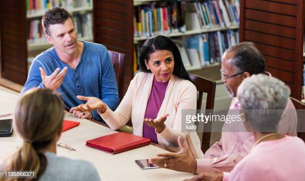 adult education class, discussion in library - debate stock pictures, royalty-free photos & images