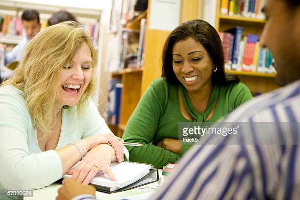 adult education: laughing mature students enjoying their studies together