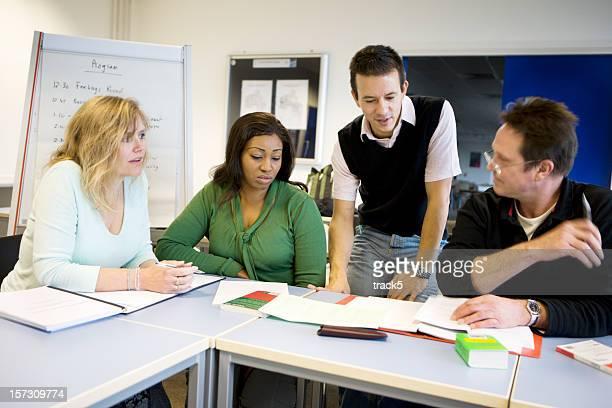 Formation des adultes: Étudiants matures débattre d'un projet avec leur professeur