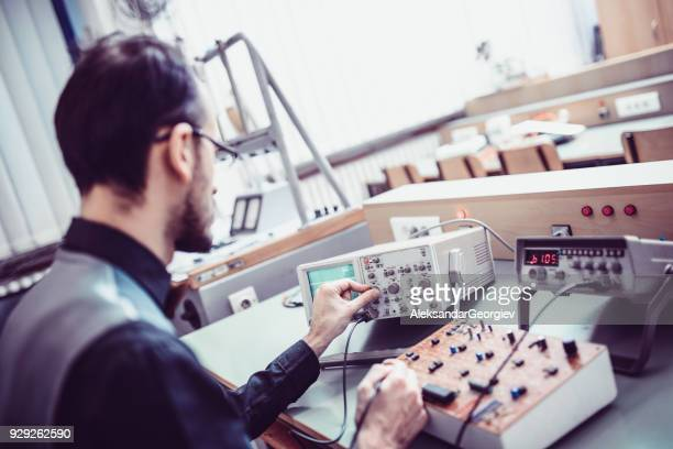 adult engineer measuring in his working office - oscilloscope stock pictures, royalty-free photos & images