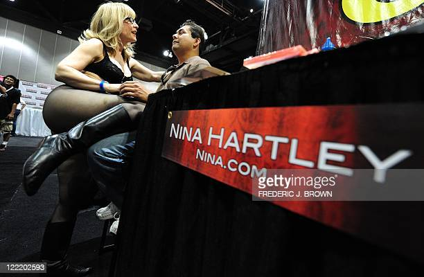 Adult entertainment industry legend Nina Hartley gets close with a fan to pose for pictures on the opening day of the 2011 Exxxotica Expo on August...