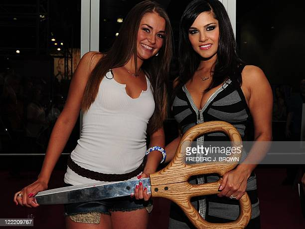 Adult entertainment industry stars Allie Haze and Sunny Leone pose with the redribbon cutting oversized scissors on opening day of the 2011 Exxxotica...