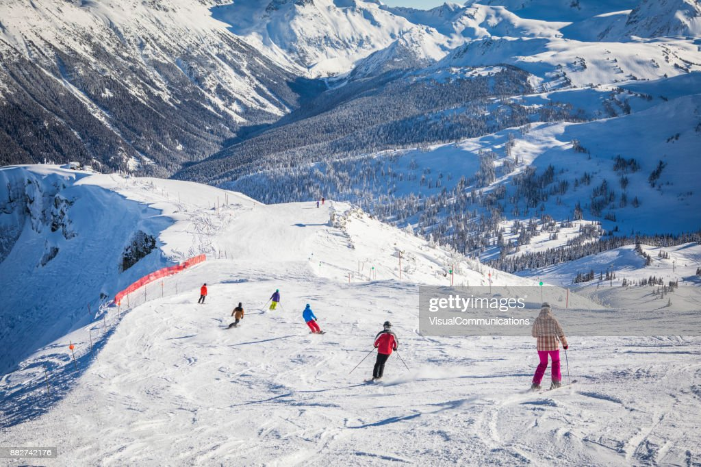 Adult family skiing and snowboarding on sunny day. : Stock Photo
