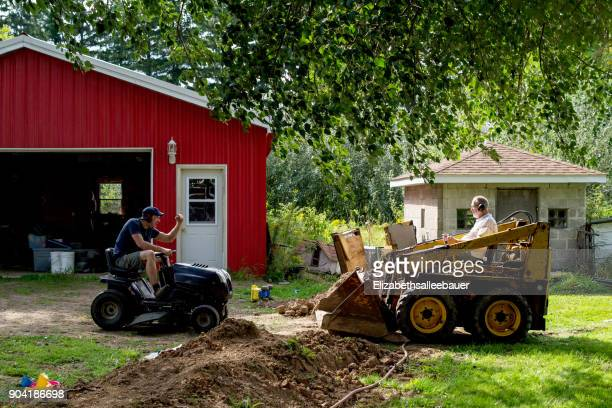 Adult father and son head to head with skid steer and lawn mower