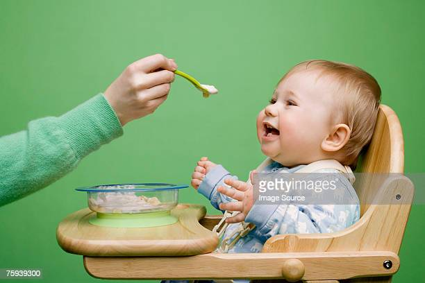 adult feeding baby - feeding stock photos and pictures