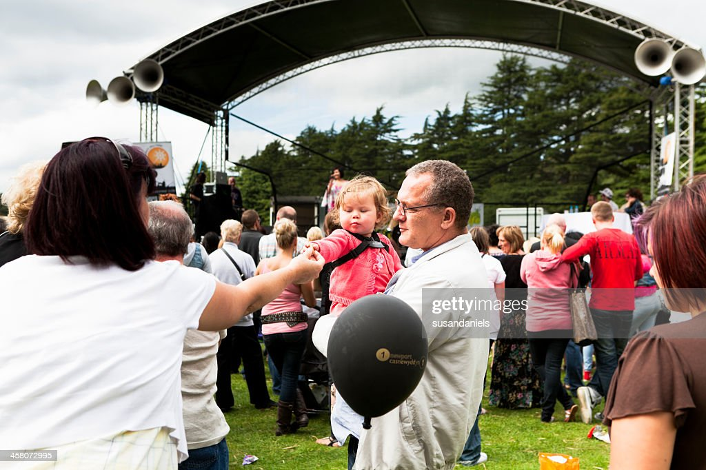 adult feeds child at the festival : Stock Photo