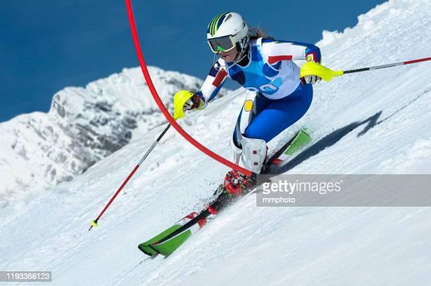 adult female alpine skier racing slalom - sport invernale foto e immagini stock